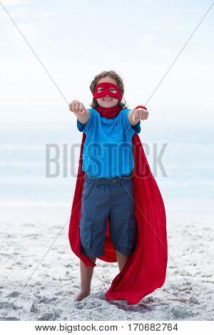 Full length portrait of happy boy in superhero costume standing at beach