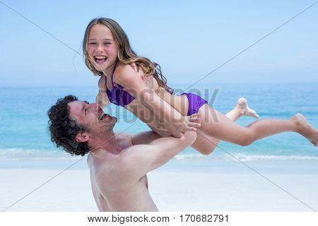 Cheerful shirtless man lifting daughter at sea shore