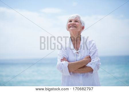 Happy senior woman with arms crossed looking up while standing at sea shore
