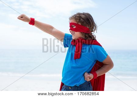 Cheerful boy in superhero costume pretending to fly at sea shore