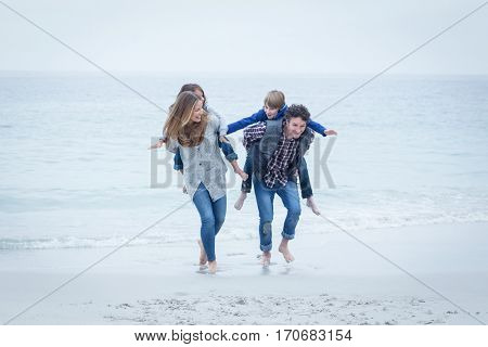 Happy parents running while carrying children on back at sea shore