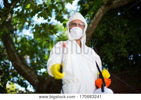 Man spraying insecticide while standing against tree in lawn