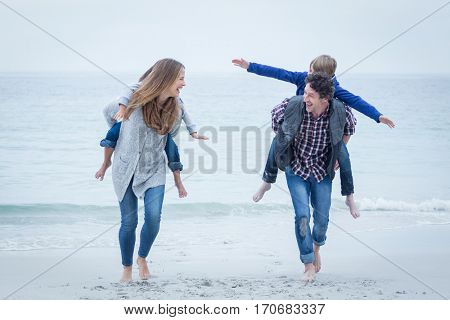 Happy mother and father carrying children on sea shore at beach