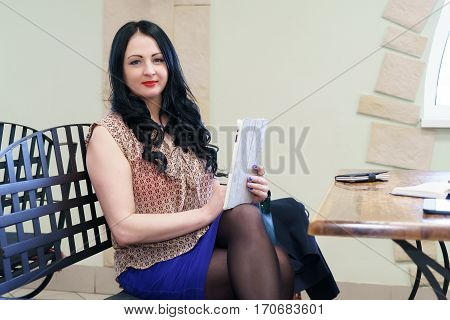 Brunette model aged 25s sitting at the table holding computer tablet poses for camera indoors