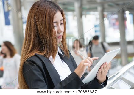 Beautiful Businesswoman working with Wireless digital Tablet in Modern city Background as Business Technology Concept.