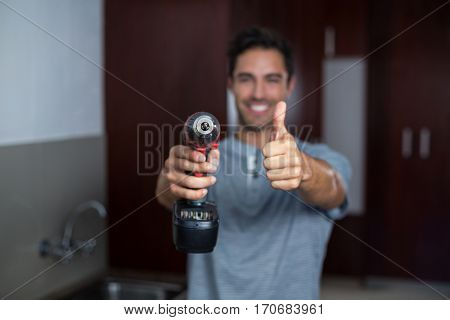 Portrait of smiling man showing thumbs up while holding cordless hand drill at home
