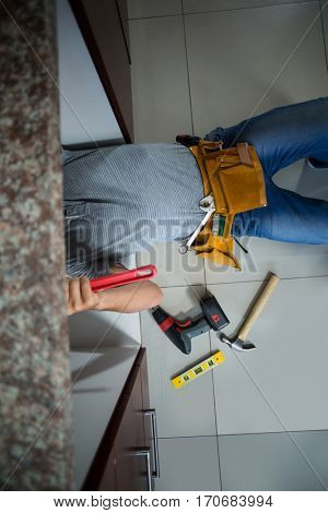 Low section of man working while lying in kitchen