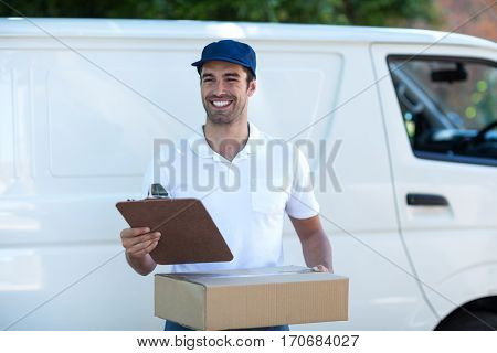 Smiling delivery man with clipboard and cardboard box while standing by van