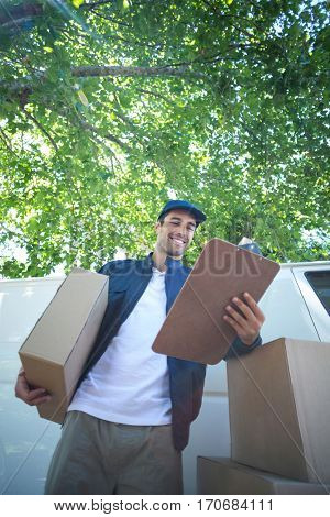 Low angle view of smiling delivery man holding clipboard while standing by van