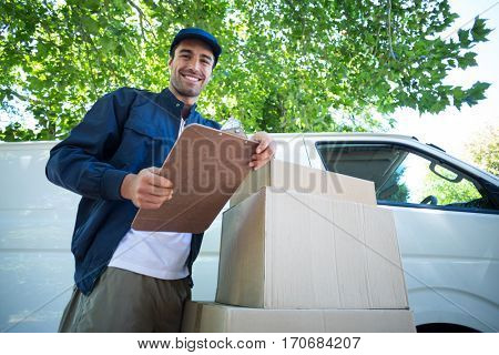 Low angle portrait of smiling delivery man holding clipboard while standing by van