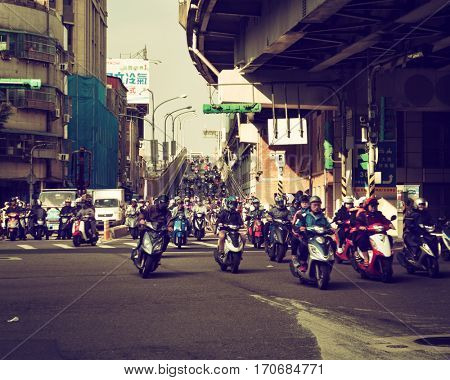 Taipei - December 2016: Street view with motorbikes on junction arriving from Taipei Bridge in the morning.