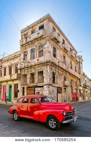 HAVANA,CUBA - FEBRUARY 3, 2016 : A vintage american car next to an crumbling old building in Havana