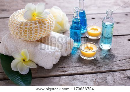 Spa or wellness setting in blue yellow and white colors. Bottles wih essential aroma oil towels candles and wisps on wooden background. Selective focus.