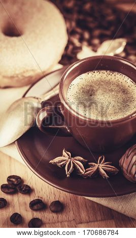 Cup fragrant hot coffee with bean chocolate sweet and loaf in vintage rustic style on wooden board for bracing morning breakfast.