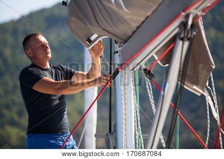 Young man skipper sets sail on a sailing yacht boat.