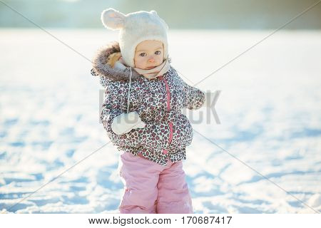 little girl walks through the snow in a warm jaket and hat