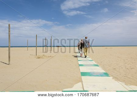 RIMINI,ITALY-APRIL 17,2015:People on pedestrian path submerged by sand on the beach in Rimini in Italy during a cloudy day