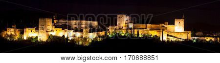 Panoramic view of the famous Alhambra Royal Palace by night from the best viewpoint. This site is known as one of the most beautiful in the world and is a Unesco heritage. Granada, Andalucia, Spain.