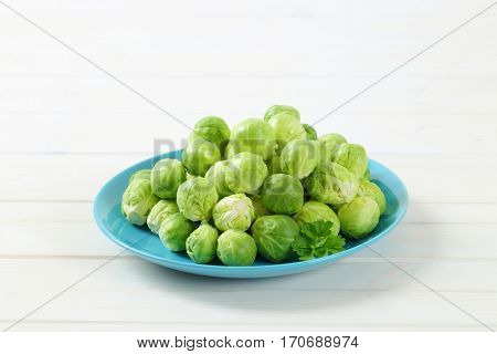 plate of raw Brussels sprouts on white background