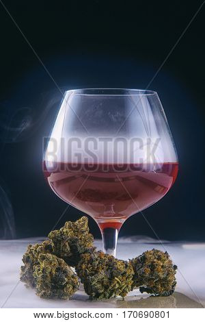 Detail of dried cannabis buds (Grandaddy Purple strain) with glass of red wine - infused medical marijuana concept background