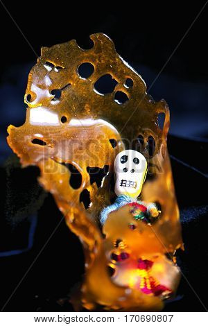 Detail of cannabis oil concentrate aka shatter (death bubba strain) isolated against black background
