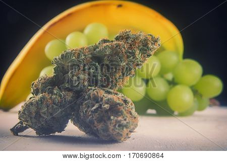 Detail of dried cannabis buds (Grape Ape strain) with fresh fruit - medical marijuana concept background
