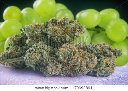Detail of dried cannabis buds (Grape Ape strain) with fresh fruit - medical marijuana concept background