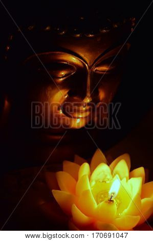 Buddha head in the dark, illuminated by a candle in the form of a lotus flower.