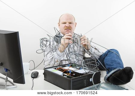 Portrait of furious businessman holding tangled cables of computer at desk in office