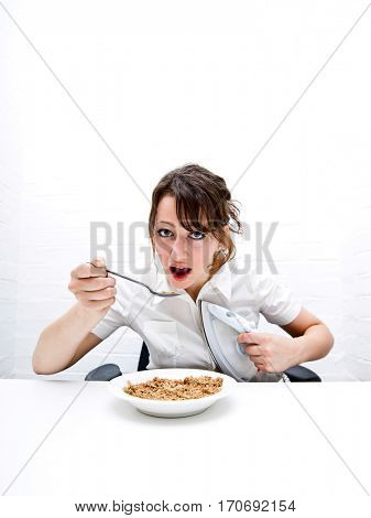 Portrait of young businesswoman ironing her shirt white having breakfast at table