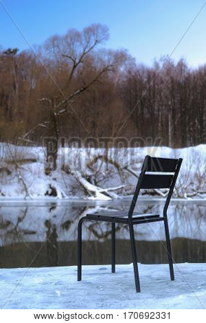 Chair on a winter river bank