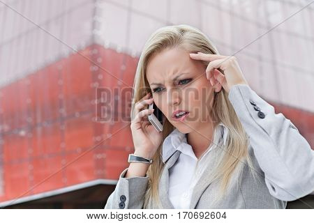 Close-up of angry businesswoman conversing on cell phone against office building
