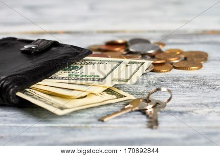 Keys and purse with money. Satisfaction with life.