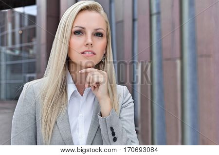 Confident businesswoman with hand on chin looking away against office building