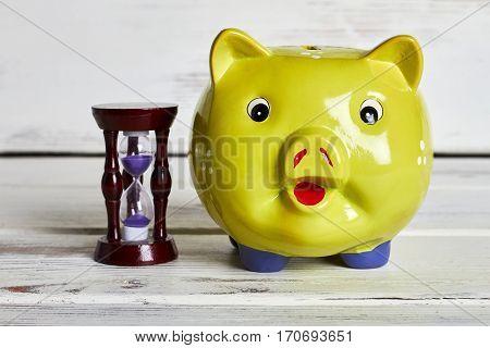 Piggu bank and sandglass. Goal is close.