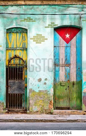 Old shabby house in Havana with a cuban flag painted on its door and the words Viva Cuba