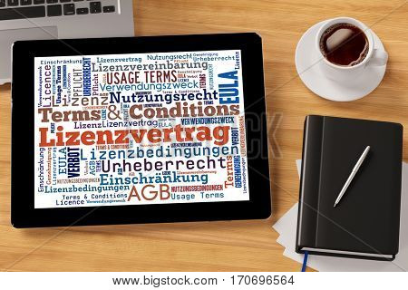 Terms and conditions tag cloud on tablet computer on desk with German words