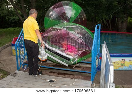 man inflates a zorb with little girl