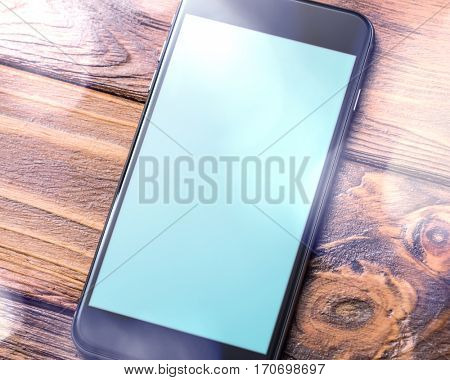 Black smartphone mock-up on table close-up. Clipping path