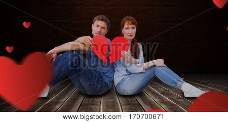 Couple holding a broken heart against floorboard against brown wall
