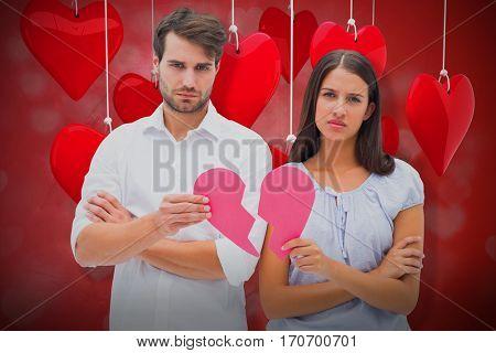 Upset couple holding two halves of broken heart against valentines heart design 3d