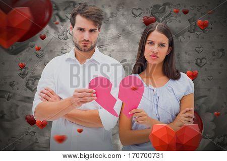 Upset couple holding two halves of broken heart against love heart pattern 3D