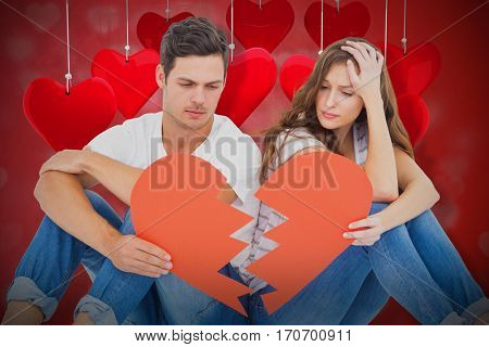 Young couple sitting on floor with broken heart shape paper against valentines heart design 3d