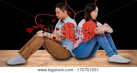 Sad couple holding broken heart pieces against red hearts floating
