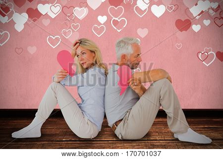 Unhappy couple sitting while holding broken heart against white background
