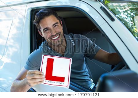 Portrait of happy man with leaning sign sitting in van