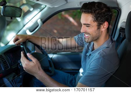 Smiling handsome driver using phone while sitting in car