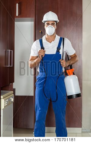 Man doing pest control in kitchen in a house