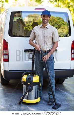 Portrait of happy janitor with vacuum cleaner standing against van