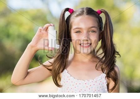 Portrait of girl holding an asthma inhaler in the park